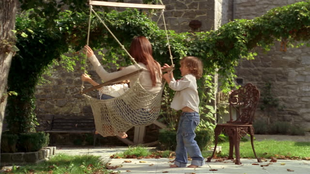 Medium shot young boy spinning mother and sister in hammock-swing in yard