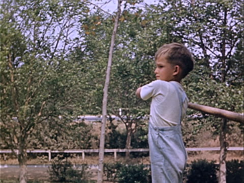 stockvideo's en b-roll-footage met 1939 medium shot young boy swinging bat during softball game in griffith park / los angeles, california, usa  - homemovie