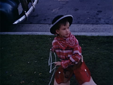 1940 medium shot young boy throwing lasso and wearing cowboy costume in street / los angeles, california, usa  - 1940~1949年点の映像素材/bロール