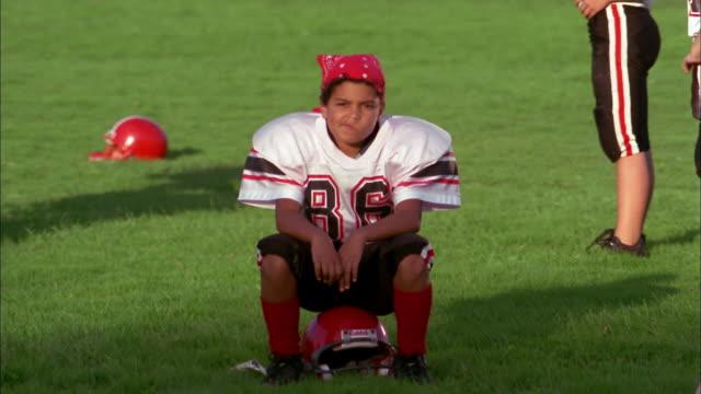 medium shot young boy wearing football uniform sitting on helmet and looking at cam - アメフトのユニフォーム点の映像素材/bロール