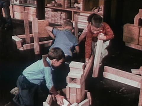 1955 medium shot young boys building w /wooden blocks / audio - art class stock videos & royalty-free footage