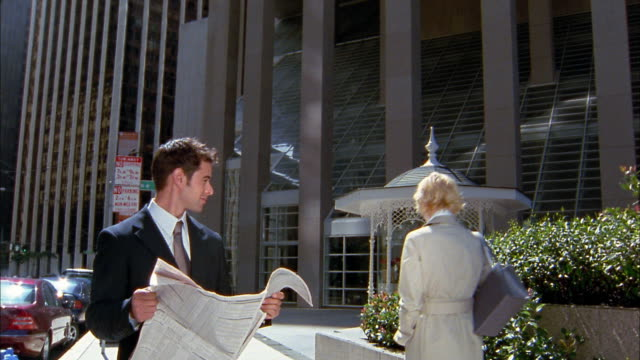 Medium shot young businessman looking up from newspaper to flirt with young blonde businesswoman passing by