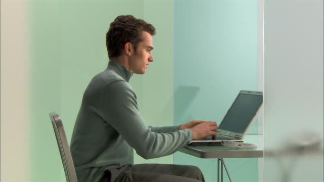 Medium shot Young businessman using laptop and talking on phone in modern office