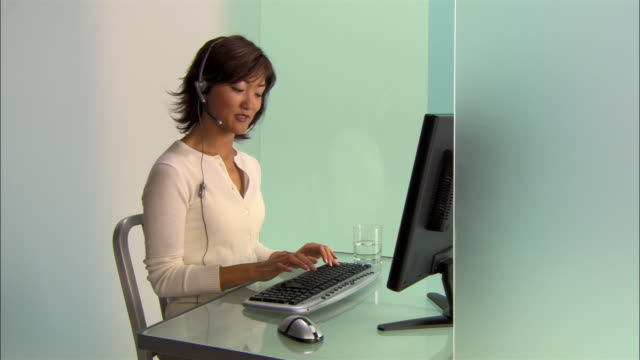 stockvideo's en b-roll-footage met medium shot young businesswoman talking on headset and using desktop computer in modern office - headset