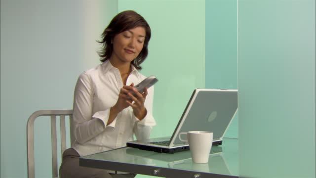 medium shot young businesswoman using laptop and talking on phone in modern office - コードレスフォン点の映像素材/bロール
