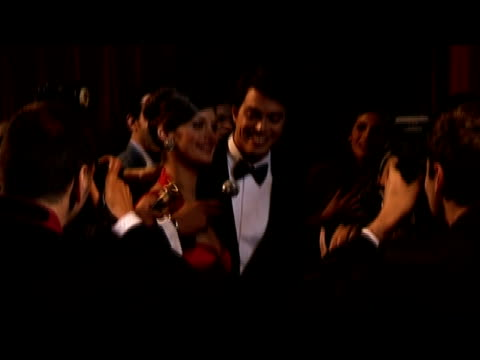 Medium shot young celebrity couple greeting paparazzi and being interviewed at red carpet event/ London, England