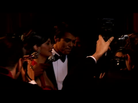 Medium shot young celebrity couple greeting paparazzi at red carpet event/ London, England