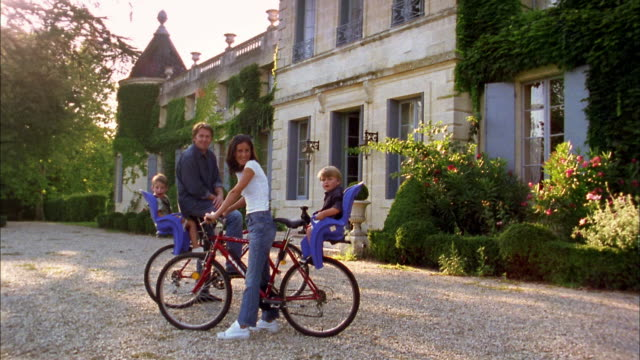 Medium shot young couple and two young boys in child seats on bicycles posing in front of chateau / France