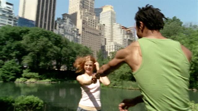 vídeos y material grabado en eventos de stock de medium shot young couple dancing by pond in central park / man picking up and spinning woman / new york - central park