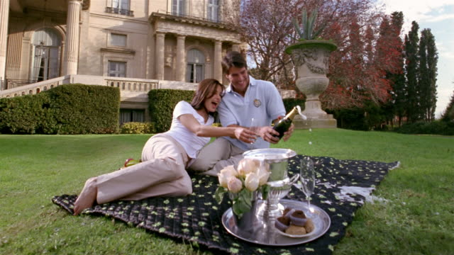 stockvideo's en b-roll-footage met medium shot young couple popping open champagne bottle during picnic on grounds outside mansion - achterover leunen