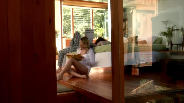 vídeos y material grabado en eventos de stock de medium shot. young couple reading in bedroom. - decoración objeto