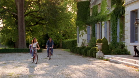 medium shot young couple riding bicycles w/two young boys sitting in child seats in front of chateau / france - castle stock videos & royalty-free footage