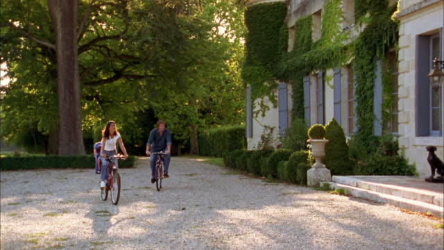 medium shot young couple riding bicycles w/two young boys sitting in child seats in front of chateau / france - in front of stock videos & royalty-free footage