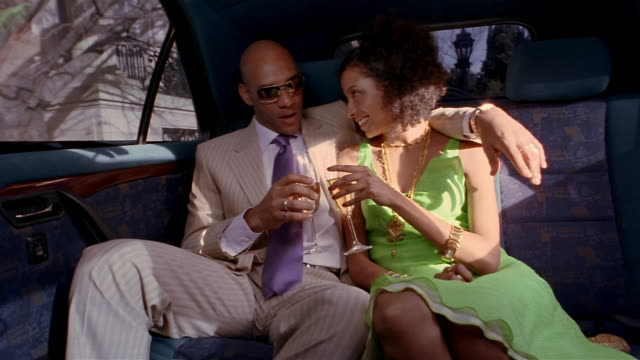 Medium shot young couple toasting and drinking champagne in the back of limousine / man kissing woman on nose