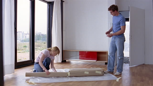 Medium shot young couple unwrapping package of wood in unfurnished apartment