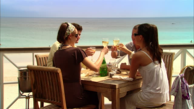medium shot young couples toasting with wine at seaside restaurant during vacation/ harbor island, bahamas - 白ワイン点の映像素材/bロール