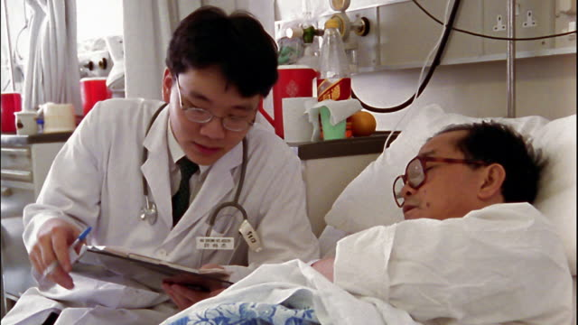 Medium shot young doctor discussing case with patient in bed / Hong Kong
