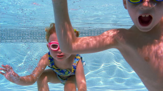 Medium shot young girl and boy swimming underwater + looking at camera