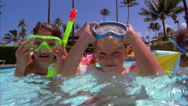 medium shot young girl and boy wearing scuba goggles in swimming pool + smiling at cam - swimwear stock videos & royalty-free footage