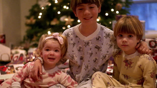 Medium shot young girl and two boys in pajamas posing in front of Christmas tree