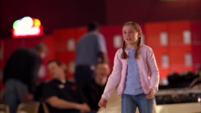 medium shot young girl bowling / cheering and hugging mother - ボウリング点の映像素材/bロール