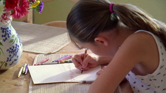 medium shot young girl coloring on paper with crayons - crayon stock videos and b-roll footage