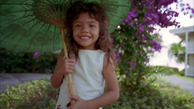 vídeos de stock, filmes e b-roll de medium shot young girl holding umbrella and covering her mouth - mãos cobrindo boca
