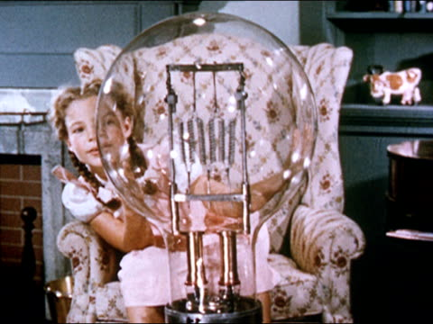 1949 medium shot young girl in chair inspects workings of oversized light bulb/ audio - filament stock videos and b-roll footage