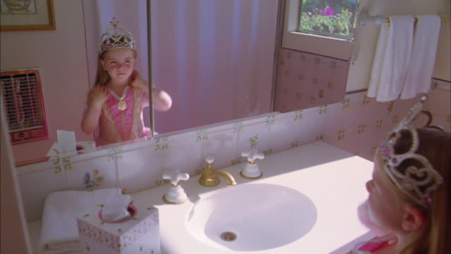 Medium shot young girl in princess dress and crown looking at herself in bathroom mirror