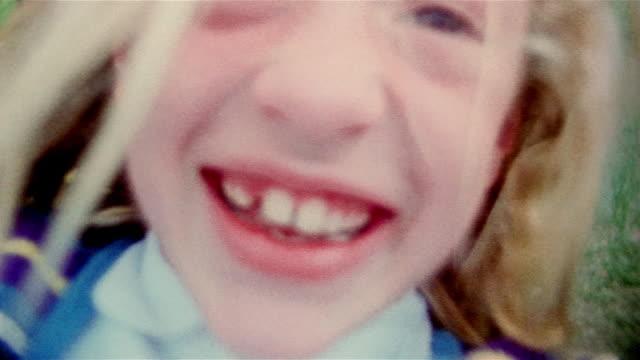 vídeos y material grabado en eventos de stock de medium shot young girl on swing / close up swing toward cam / cu on face / iowa - columpiarse