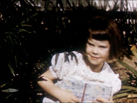 1954 Medium shot young girl peeking out from behind shrub / AUDIO