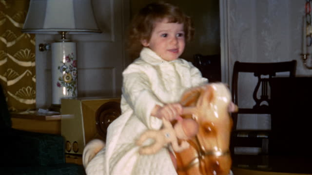 1953 medium shot young girl riding on rocking horse and holding doll