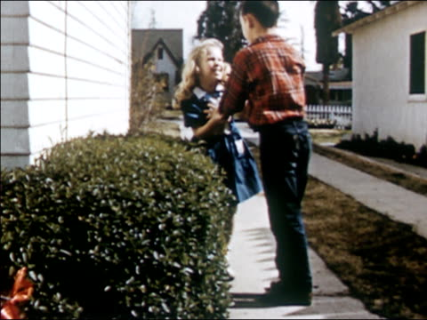 stockvideo's en b-roll-footage met 1954 medium shot young girl running and boy chasing behind her / girl hiding in bushes / boy catching and stopping girl and sending her back in other direction / girl coming out from bushes and boy shushing her - zus