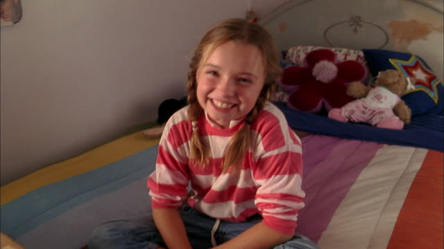 medium shot young girl sitting on bed and smiling at cam - one girl only stock videos & royalty-free footage