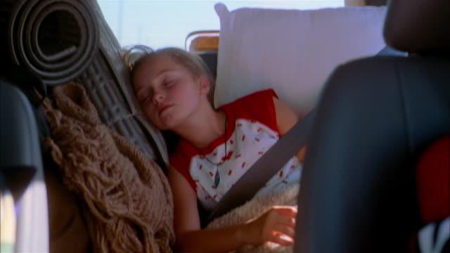 Medium shot young girl sleeping in backseat of minivan