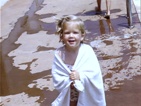 1952 medium shot young girl standing poolside wrapped in beach towel / beverly hills, california, usa  - 1952 stock videos & royalty-free footage