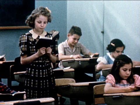 vídeos de stock e filmes b-roll de 1949 medium shot young girl standing up in school room and reading as other children sit at their desks/ audio - 10 11 anos
