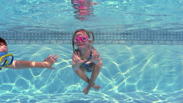 medium shot young girl underwater with boy swimming by in foreground - swimwear stock videos & royalty-free footage