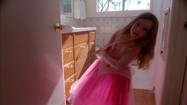 medium shot young girl wearing and adjusting her dress in bathroom - one girl only stock videos and b-roll footage