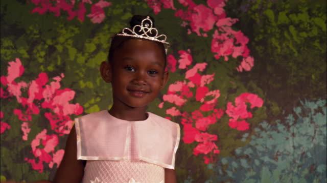 Medium shot young girl wearing tiara and carrying wand dancing and twirling