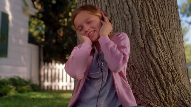 medium shot young girl w/headphones singing outdoors - compact disc player stock videos & royalty-free footage