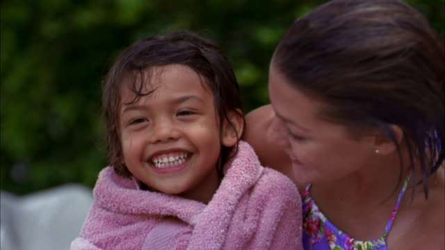 Medium shot young girl wrapped in towel beside mother / smiling at CAM