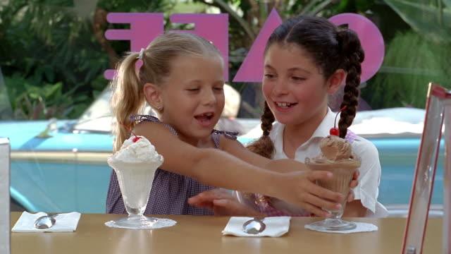 medium shot young girls being served ice cream and exchanging sundaes / eating + smiling / miami, florida - サンデー点の映像素材/bロール