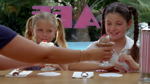 Medium shot young girls being served ice cream / one girl eating cherry off the other's sundae / Miami, FL
