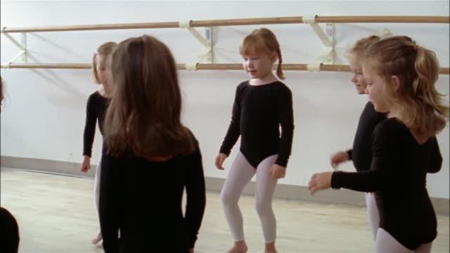 vídeos y material grabado en eventos de stock de medium shot young girls in leotards and tights doing movements and sitting down in ballet class - barra de deportes