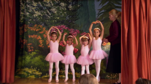 Medium shot young girls in tutus peeking out from behind curtain / zoom out walking out on stage and performing turns w/ help from teacher / curtsying as woman in audience takes photo