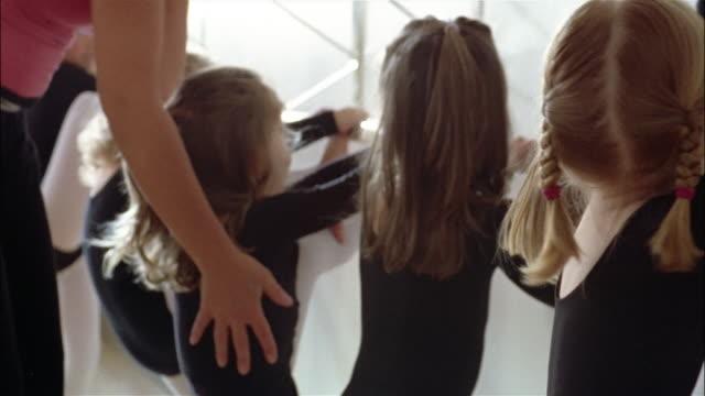vídeos y material grabado en eventos de stock de medium shot young girls wearing leotards at the barre in ballet class - barra de deportes