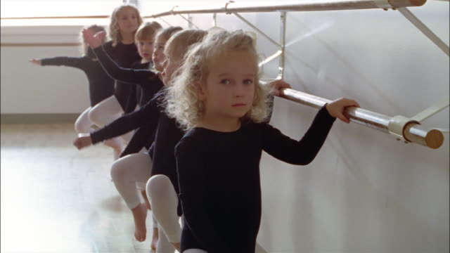medium shot young girls wearing leotards standing at the barre in ballet class - barre stock videos and b-roll footage