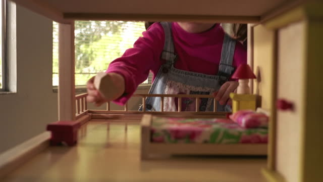 medium shot young hispanic girl bending down and putting miniature television in dollhouse - dollhouse stock videos & royalty-free footage