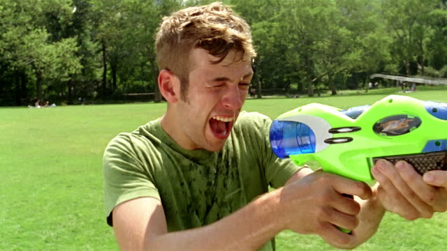 medium shot young man aiming and firing squirt gun at person squirting water back at him in park / new york - squirt gun stock videos and b-roll footage